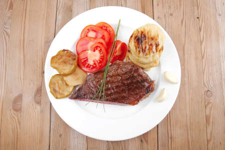 meat savory : grilled beef fillet mignon served on white plate with tomatoes and potatoes on wooden table photo