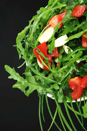 vegetable food : green salad with raw tomato and garlic in white bowl on black background photo