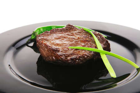 black dish: meat food : roasted fillet mignon on black plate with chili pepper and chives isolated over white background
