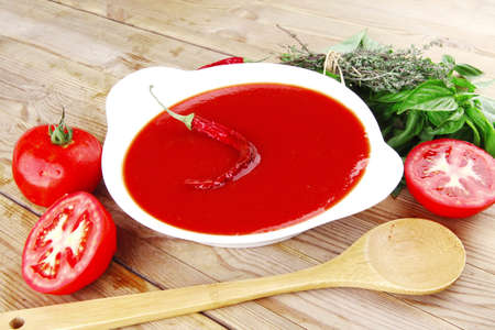 hot fresh diet tomato soup with basil thyme and raw tomatoes in white round bowl over red mat on wood table ready to eat photo