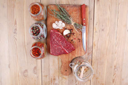 fresh raw beef meat fillet flesh with peppercorn and thyme ready to grill on wood figured old style board  over table with spices in glass photo