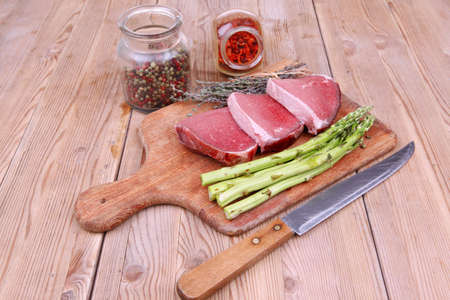 meat food : raw beef fillet on cutting board with asparagus and thyme bundle , with color peppercorn mix and red paprika powder mixed with dry spices ready to cooking photo