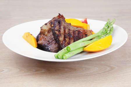 meat food : grilled red beef fillet with mango tomatoes and asparagus , served on white dish over wooden table Stock Photo - 11234428