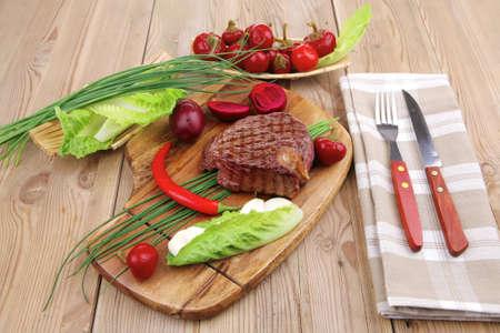 los alimentos de carne: carne asada con guarnici�n de personal de verde y rojo pimiento picante de chile en la mesa de madera con cubiertos Foto de archivo - 11234524