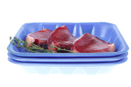 uncooked raw beef fillet with thyme twig on blue tray isolated over white background photo