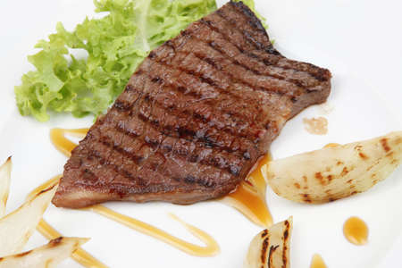 meat food : roast steak boneless with roast onion, served on green lettuce salad on dish isolated over white background Stock Photo - 11251280