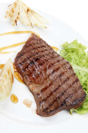 meat food : roast steak boneless with roast onion, served on green lettuce salad on dish isolated over white background photo