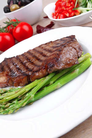 meat table : grilled beef fillet with asparagus , pasta portion , tomatoes and several kinds of olives served on white dish over light wood Stock fotó