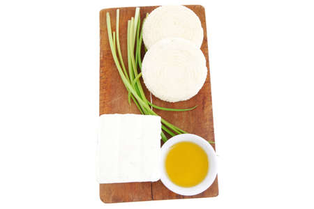 dairy food : feta white cheese cubes with olive oil on small saucer on cut wooden plate isolated over white background photo