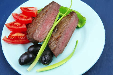 meat food : roasted fillet mignon on blue plate with pepper tomatoes and black greek olives over blue wooden table photo