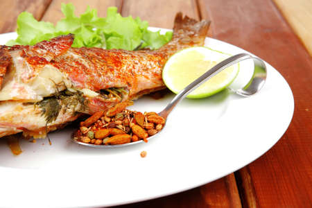 main portion of two grilled fish served on plate with tomatoes and spices photo