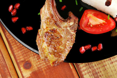 main course: grilled ribs with rice and tomatoes on black dish over wood photo