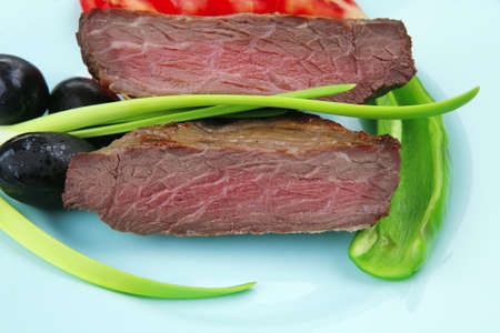 meat food : roast beef fillet mignon served on blue plate with chili pepper and tomatoes over blue wooden table photo