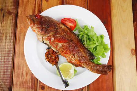 savory on wood: fried fish served with tomatoes lemon and spices photo