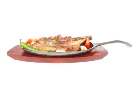 alcaparras: fresca la carne asada de carne chuletón en el plato de metal de hierro con la pimienta roja picante y tomate aisladas sobre fondo blanco Foto de archivo