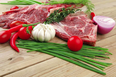 fresh spare ribs : raw lamb with thyme , red chili pepper , tomato , garlic , and chives over wooden table photo