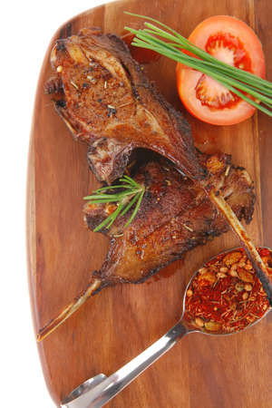 meat over wood: grilled ribs on plate with tomatoes and spices isolated on white background photo