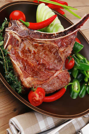 savory : roasted beef spare rib on dark dish with cutlery thyme pepper and tomato on wooden table Stock Photo - 11473087