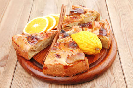 sweet food : apple pie cuts served on wooden plate over table with cinnamon and lemon photo