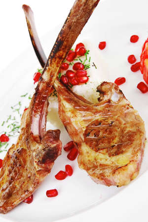main course: grilled ribs with rice and tomatoes on white plate over white background photo