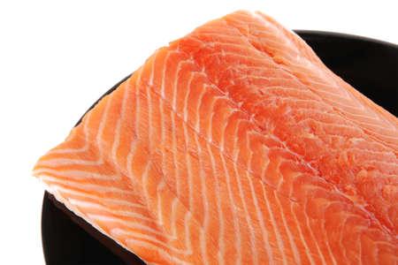 big salmon chunk on black plate over white photo