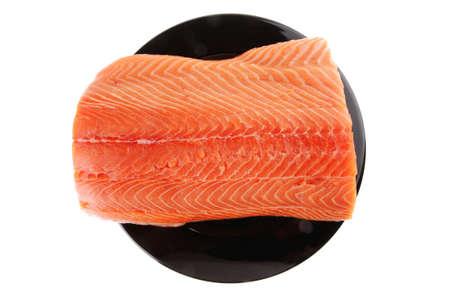 fresh raw salmon fillet on black over white photo