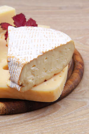 edam parmesan and brie cheese on wooden platter over wooden table photo