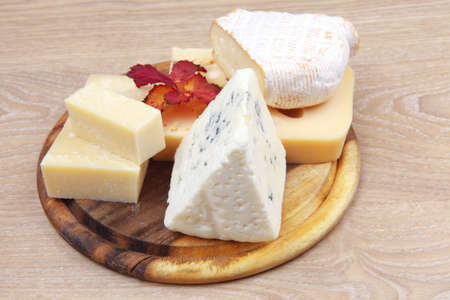 various types of cheese on wooden platter over wooden table Stock Photo - 11530611