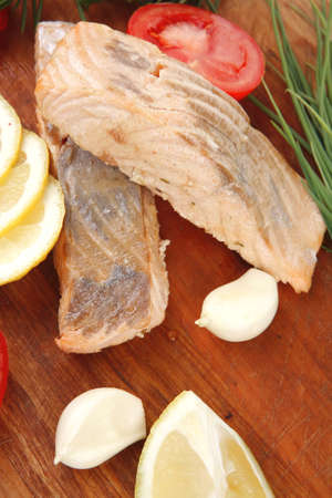 sea food : roasted pink salmon fillet with chinese onion, cherry tomatoes pieces , rosemary twigs and lemon on wooden board isolated over white background Stock Photo - 11530464