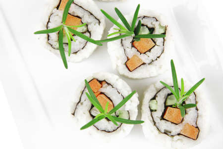 Japanese Cuisine - California Sushi Roll with Avocado, Cream Cheese and Raw Salmon inside. With wasabi and ginger. isolated over white background photo