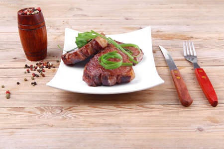 grilled meat beef steaks strips on white plate with pepper and cutlery over wood table photo