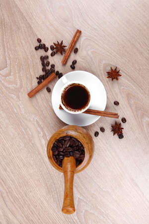 sweet hot drink : black Turkish coffee in small white mug with mortar and pestle , coffee beans over a wooden table , decorated with cinnamon sticks and anise stars photo