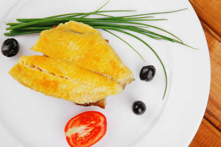 roasted fish fillet with tomatoes,chives and bread on plate over wooden table Stock Photo - 11635222