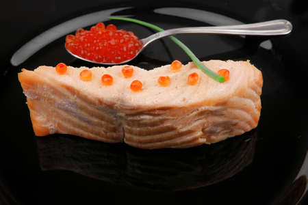 savory fish : norwegian salmon fillet roasted with green onion pen , red caviar in spoon , on black dish isolated over white background Stock Photo - 11635245