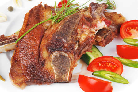 fresh roasted lamb meat fillet ready on china plate with tomatoes, green pepper , and garlic isolated  over white background photo