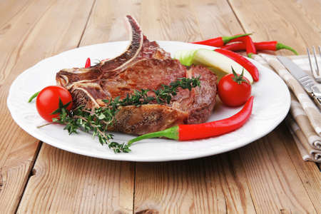 meat food : grilled beef spare rib on white dish with thyme pepper and tomato on wooden table photo
