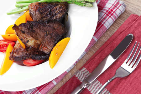 frame less: meat food : rare medium roast beef fillet with mango tomatoes and asparagus , served on white dish on red table map over wooden table Stock Photo