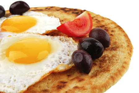 fried eggs on pancake over white with vegetables photo
