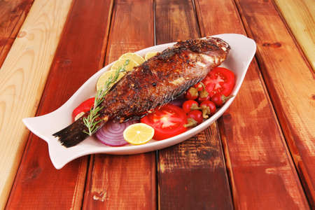 main course: whole fryed sunfish on wooden table with lemons and peppers Stock Photo - 11777929