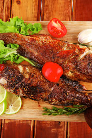 roasted sea fish and castors on wood with tomatoes, lemon and green lettuce salad Stock Photo - 11777878