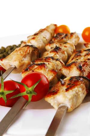 pork shish kebab on white platter with vegetables