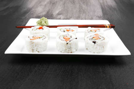 Maki Sushi - California Roll made of Fresh raw Salmon, Cream Cheese and Avocado inside. Served with wasabi . over black table . on square white plate photo