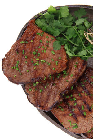 fresh grilled red meat with thyme on metal pan isolated on white background photo