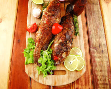 roast golden fish served on wooden table with lemon tomatoes and salad photo