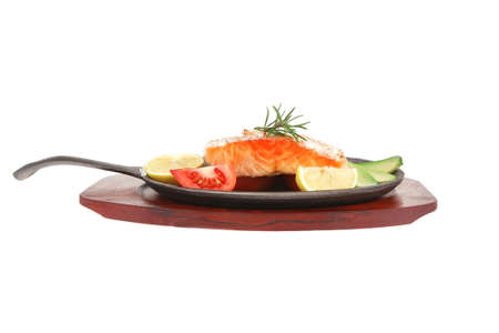 food: roast salmon on metal pan over red wooden plate isolated over white background photo