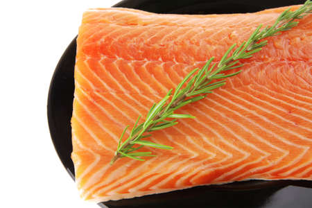 fresh uncooked red fish fillet on black over white with rosemary Stock Photo - 11794320