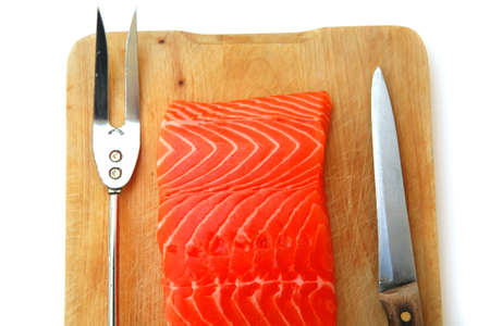 fresh raw salmon fish piece over wooden board isolated on white background photo