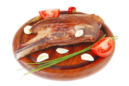 fresh hot roasted lamb meat fillet ready on red wooden plate with tomatoes, green pepper , and garlic isolated over white background Stock Photo - 11903888