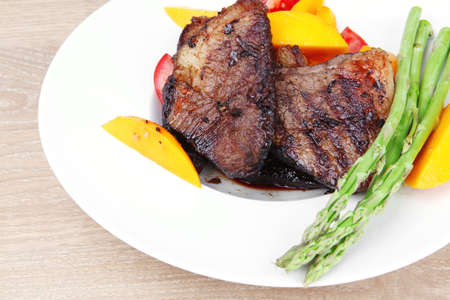 meat food : rare medium roast beef fillet with mango tomatoes and asparagus , served on white dish over wooden table Stock Photo - 11902777