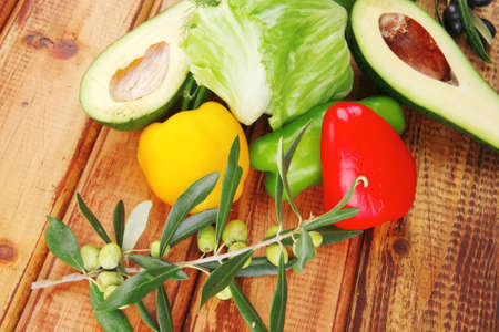 vegetables and raw olives over wooden tables photo